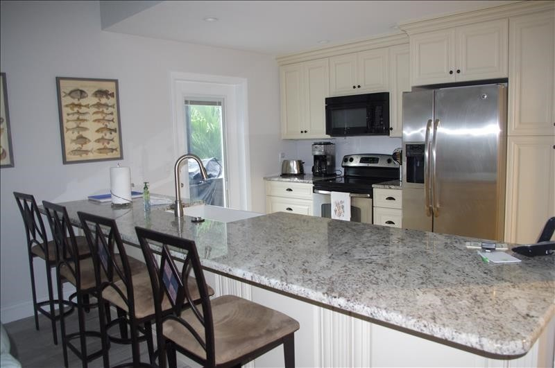 The kitchen features granite countertops and seating for 4.