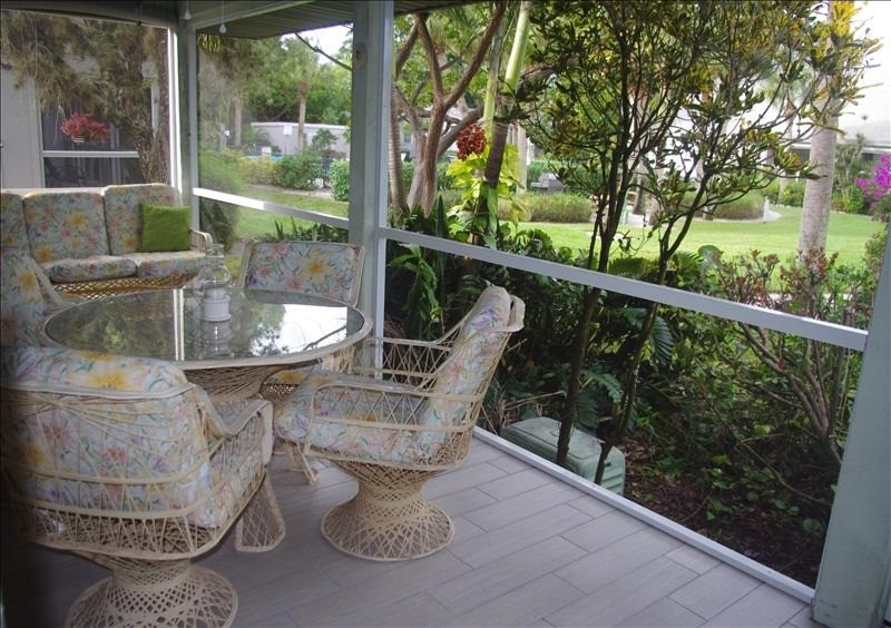 The screened lanai overlooks the garden and tennis courts.