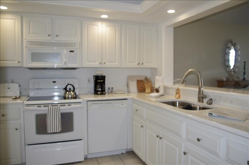 Fully equipped kitchen has quartz countertops