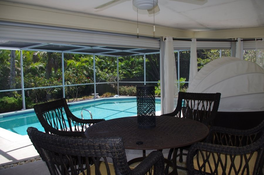 The screened lanai has a grill and outdoor dining area.