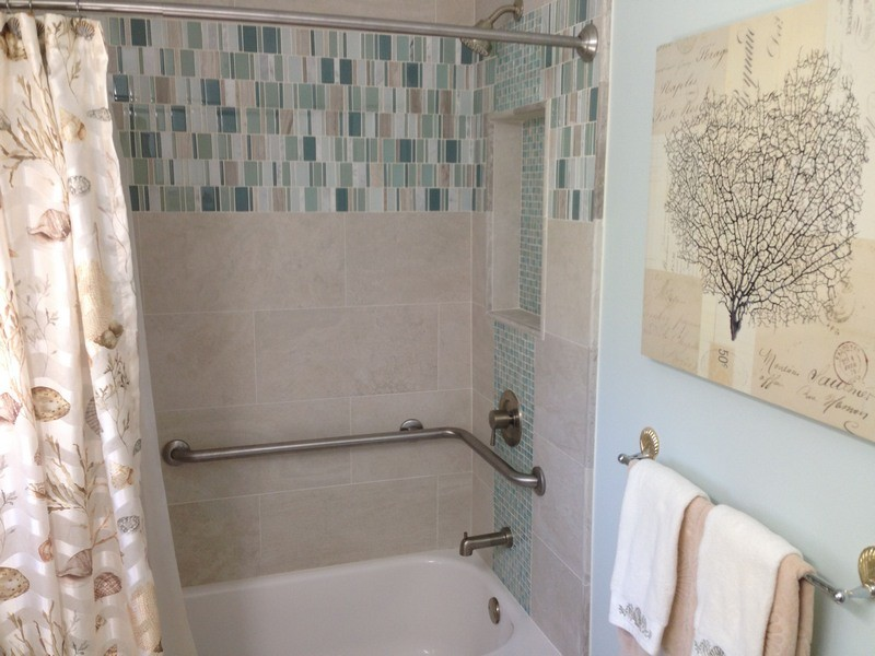 The master bath has a tub/shower unit with safety hand rails